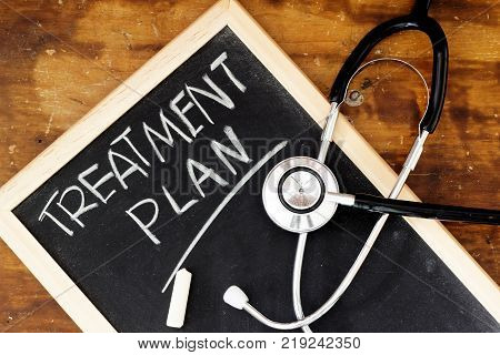 TREATMENT PLAN word written on chalkboard with stethoscope and chalk on it.