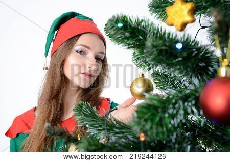 Young Female Model Christmas Photo Session. Twenty Years Old Girl In Elf Costume Standing Next To Ch