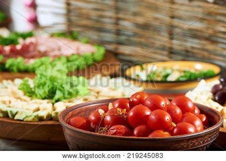 Close up of a tasty red marinated tomatoes on the colorful background with different marinated vegetables and appetizers, decorated with fresh lettuce leaves.
