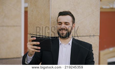 Businessman talking on tablet computer having video chat with his wife. Businessman using app to have video conference conversation with family during break
