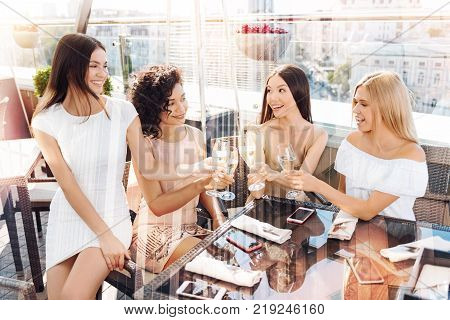 Pleasurable time. Happy delighted young women holding glasses with champagne and smiling while meeting in the restaurant poster