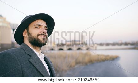 Young bearded tourist man in hat and coat watching cityscape and daydreaming while standing on riverside near river