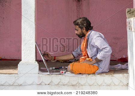 VARANASI INDIA - JANUARY 25 2017 : Artist working on painting in ghats of the Ganges river in Varanasi India . Close up