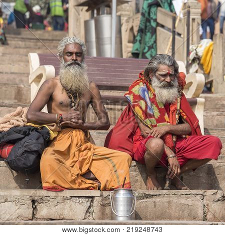 VARANASI INDIA - JANUARY 26 2017 : Two Shaiva sadhu holy man sit on the ghats of the Ganges river in Varanasi India