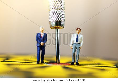 miniature businessmen standing on the dartboard with Darts arrow in center of the target. Target business concept.