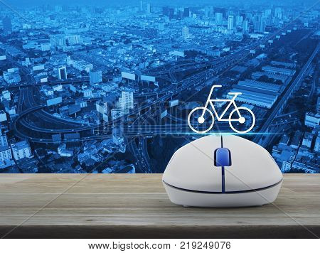 Bicycle flat icon with wireless computer mouse on wooden table over city tower street and expressway Business internet bicycle service concept
