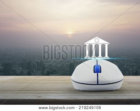 Bank icon with wireless computer mouse on wooden table over modern city tower at sunset vintage style Business banking online concept