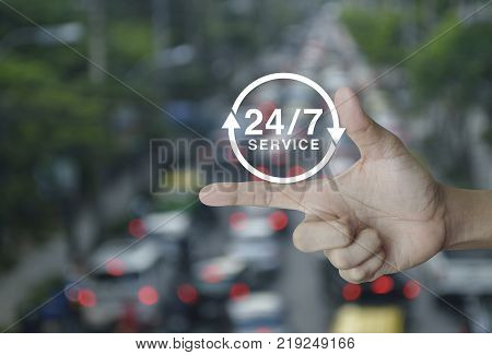 24 hours service icon on finger over blur of rush hour with cars and road Full time service concept