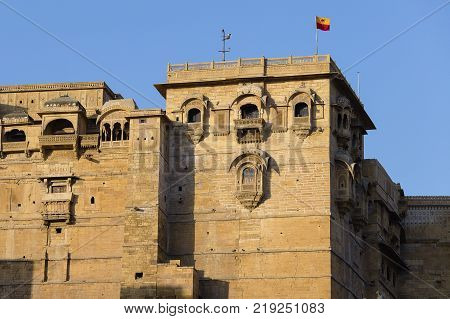 Tilt shot of Jaisalmer Fort sandstone wall with its elaborate sculpted columns windows and balconies in the morning. India