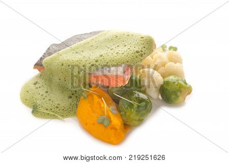 Molecular modern kitchen of red fish and vegetables under a frothy sauce on a white background, close-up