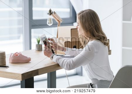 side view of young businesswoman using digital tablet at table