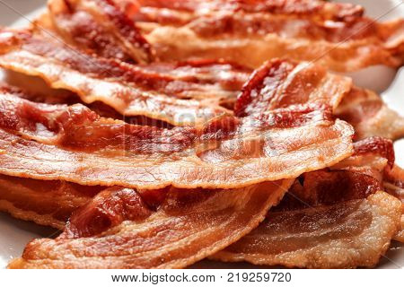 Cooked bacon rashers on plate, closeup