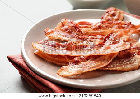 Plate with cooked bacon rashers on table, closeup