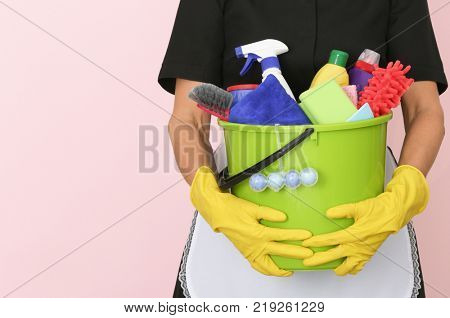 Charwoman with cleaning supplies on color background, closeup