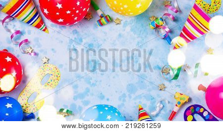 Bright colorful carnival or party scene frame of balloons, streamers and confetti on blue table. Flat lay style, birthday or party greeting card with copy space and bokeh lights