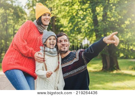 Enjoying good atmosphere. Family harmony. Happy family walk in green park have happy expressions. Affectionate father points with fore finger into distance as tries to show beautiful sunset