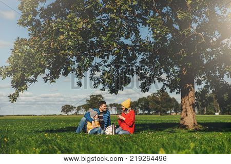 Happy family have autumn picnic sit on green grass drink hot tea communicate with each other enjoy calm atmosphere admire blue sky and beautiful landscapes. Friendly family members together