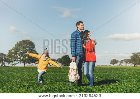 Young couple in love stand on green grass embrace and look pensively. Playful small child enjoys freedom runs on field plays near her parents has good mood and recreation. Peope and nature