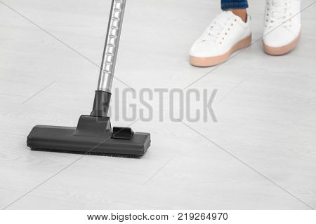 Woman hoovering floor with vacuum cleaner at home