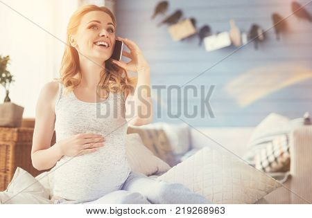 Happy mother. Overjoyed delighted pregnant woman talking on cellphone and touching her belly while enjoyign maternity leave