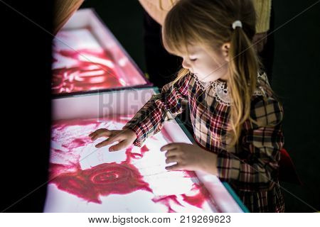 Happy little kid girl in red dress drawing by fingers on bright pink sand animation. Funny child having fun indoors