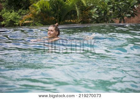 Happy young woman relaxing by the luxury swimming pool. Bali, Indonesia.