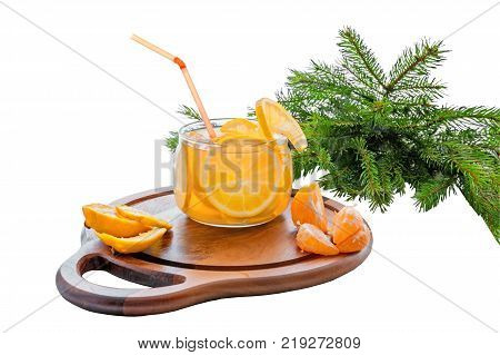 Orange cold drink with ice, lemonade with slices of orange and Mandarin in a transparent glass on a wooden stand on a background of green fir branches. Isolated on a white background. The horizontal frame.