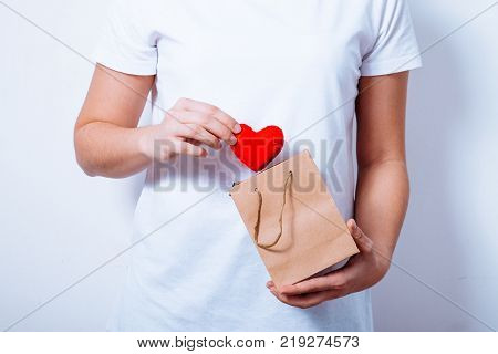 woman put heart in pocket for valentines day close up