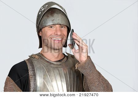 Man wearing armour holding mobile telephone