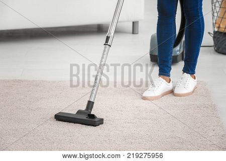 Woman hoovering carpet with vacuum cleaner at home