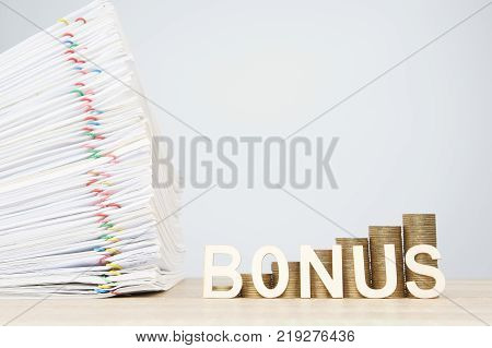 House and step pile of gold coins with overload document report of sale and colorful papercilp on wooden table with white background and copy space. Business and finance concept rich and successful.