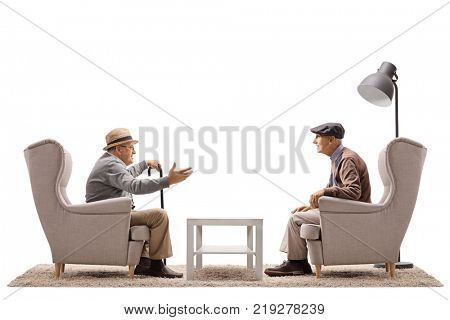 Two elderly men seated in armchairs having a conversation isolated on white background