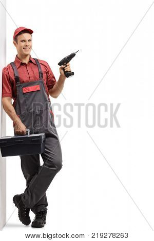 Full length portrait of a repairman with a toolbox and a drill machine leaning against a wall isolated on white background