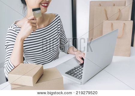 Happy Woman using smart phone and credit card register payments online shopping and customer service network connection market using technology on laptop Internet Online shopping or banking concept.