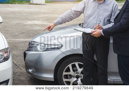 Insurance Agent examine Damaged Car and filing Report Claim Form after accident Traffic Accident and insurance concept.