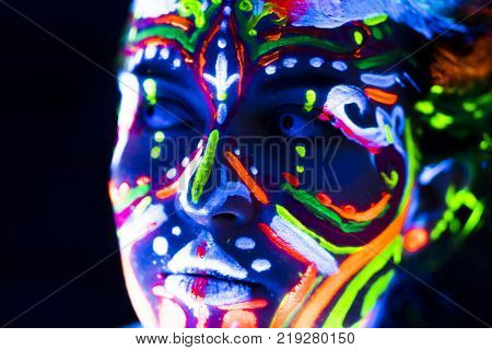 Close-up Portrait of an attractive young girl in bright blacklight bodyart