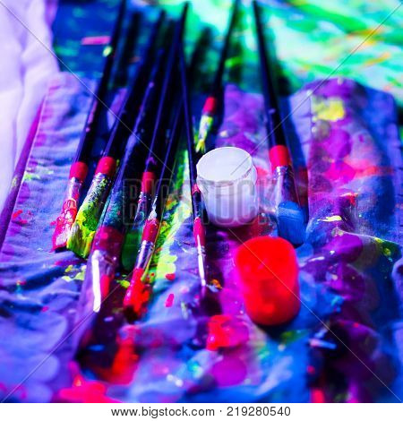 Ultraviolet dyes and brushes in blacklight. Working process. Bright UV painting poster