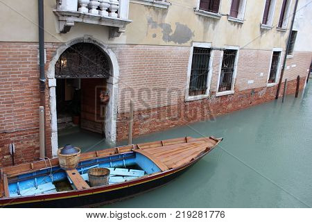 Boat parked on canal with wooden barrels. Old venetian house with wooden boat parked near. Venice city scene with boat.