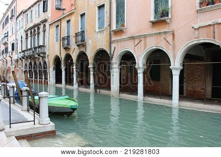 Venetian palace with arched patio on canal. Venetian canal with parked boats and old buildings. Winter town of Venice.