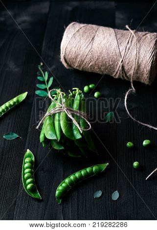 Bunch of fresh mature pods of green peas tied with rope on black wooden background. Bio healthy food. Green peas pods pea leaves and twine on wooden table
