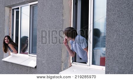 Young Man Talks With A Neighbor Through The Window. Young Man Smokes A Cigarette And Talks With A Ne