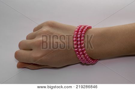 A graceful pink bracelet on a woman's hand. Hand on a gray background