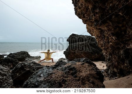 Woman in rain coat doing stand yoga asana on ocean beach during storm. Concept of yoga travelling on Bali