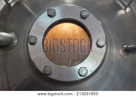 close up porthole window in factory tank