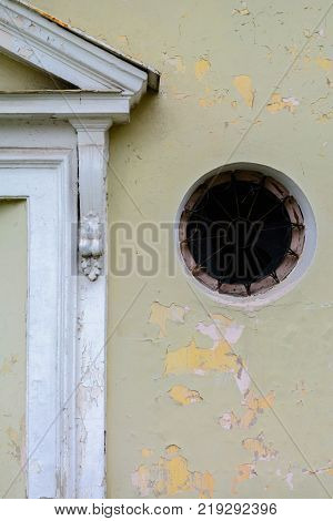 Round old window with a lattice and broken glass. Need repair and restoration