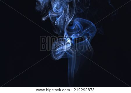 Blue ink in freeze motion powder splatted explosion. Smoking cloud backdrop. Abstract background with smoke. Blue smoke on black background. Spirit and ghost miracle.