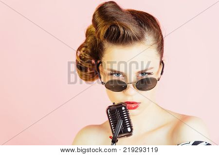 Music look and retro style pinup. Pin up young girl on pink background radio. Woman singer with stylish retro hair and makeup. Beauty and vintage fashion. Girl in glasses sing in microphone.