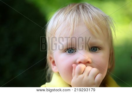 Baby infant with blue eyes on cute face and blond hair on natural environment. Child childhood family. Innocence infancy future concept