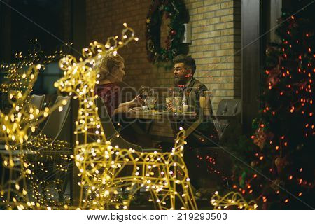Happy family celebrate new year and christmas. Couple in love enjoy xmas cuisine food wine. Winter season romance. Woman and man in restaurant with festive decorations. Holidays celebration concept.
