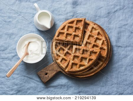 Whole wheat breakfast viennese waffles cream and milk on blue background top view